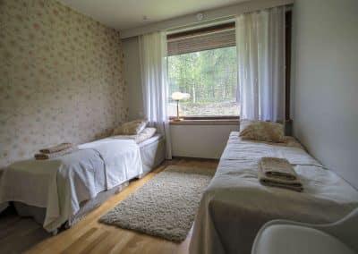 Makuuhuone kaksi sänkyä kukkatapetti