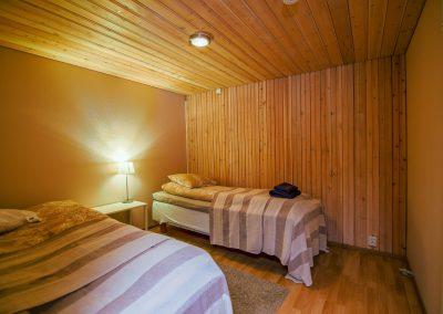 Makuuhuone kaksi sänkyä yöpöytä lampulla